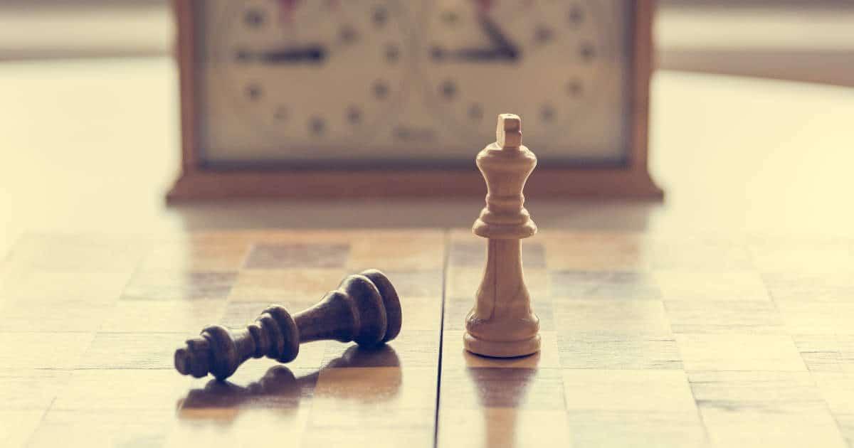 Schachbrett mit um geworfenen König und Schachuhr im Hintergrund - bildlich für Gewerblicher Rechtsschutz